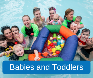 Babies and Toddlers (Image of two of our swim school instructors with a group of parents holding their babies and toddlers in their arms in our pool, in the middle of the group is a colourful floating ring holding lots of colourful balls and toys)