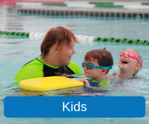 Kids (Image of one of our swim school instructors in the pool with two kids that are about 4 years old, the little girl is wearing pink goggles and is laughing, the boy is wearing blue goggles and a blue and green rashie shirt, he's holding a yellow kickboard.)
