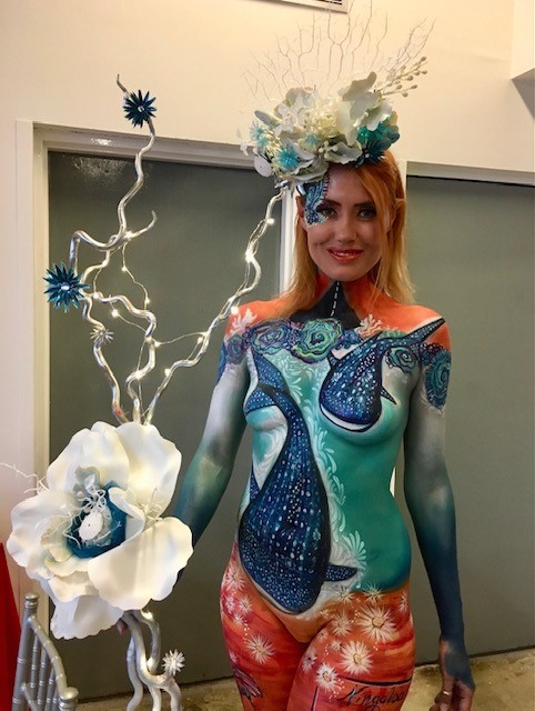 A lady with body painting of a ocean scene with whales, holding a large white flower and wearing a blue and white flower head piece.