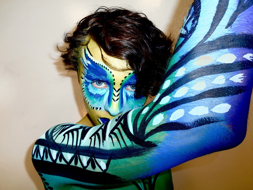 Close up of face and upper body of a person with body paint in blue, green, black and white and looks a bit like feathers.