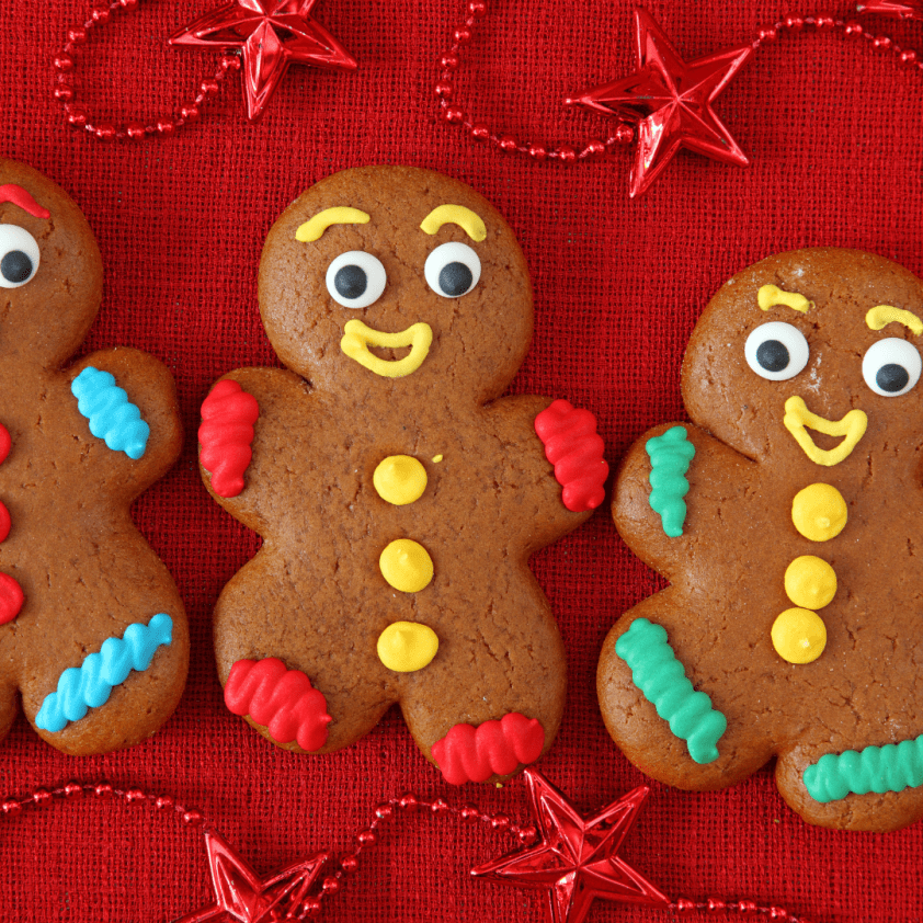 Three decorated gingerbread people on a red background