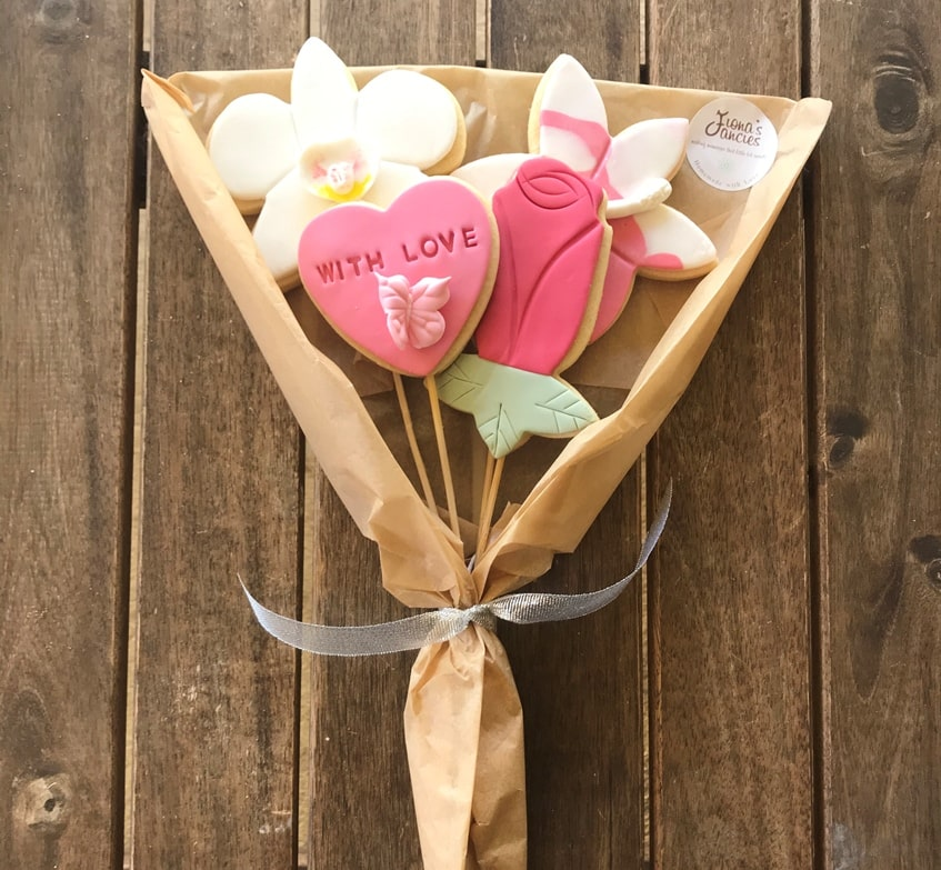 Cookies decorated as flowers in a bouquet, wrapped with brown paper and a white ribbon.