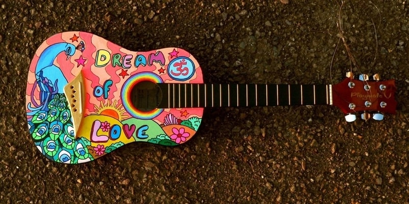 Colourful cartoon drawing on a guitar pictured lying face up on a road.