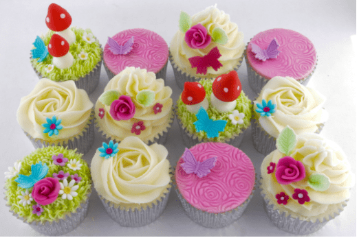 A dozen cupcakes with white, pink, green, red and blue decorations to look like a garden and flower scene.