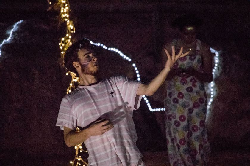 Actor performing at night with fairy lights in the background