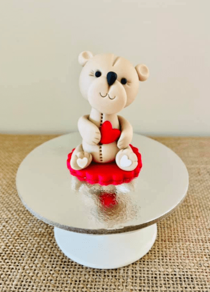 A white fondant teddy bear with a red love heart sitting on a silver pedestal.