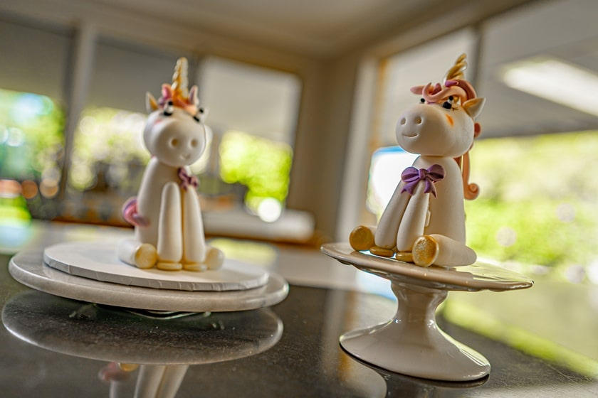 Two white unicorn fondant cake toppers sitting on pedestals.