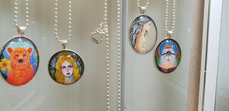 Necklace pendants hanging in a glass case