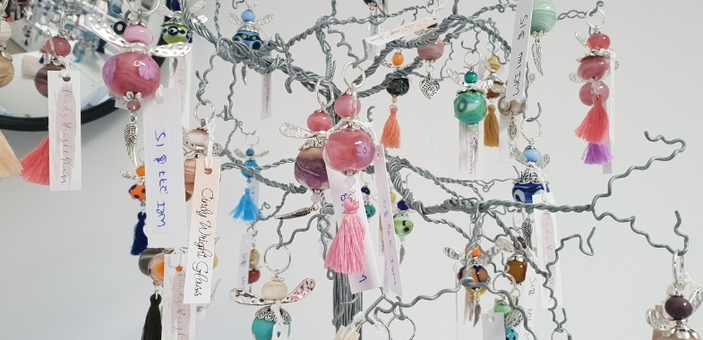 Decorated glass beads hanging from a small tree ornament
