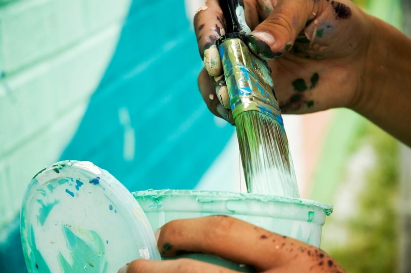 Close-up of a paintbrush with white paint being wiped on the side of a paint can or pot.