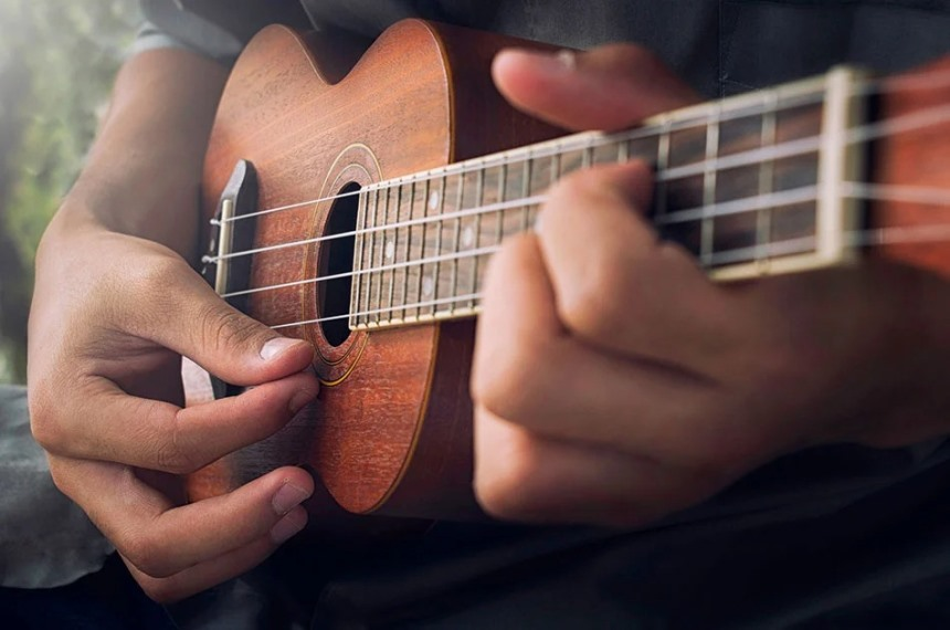 person playing a ukulele with their hands