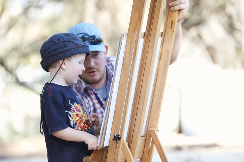 Father and son looking at a painting easel and canvas outside