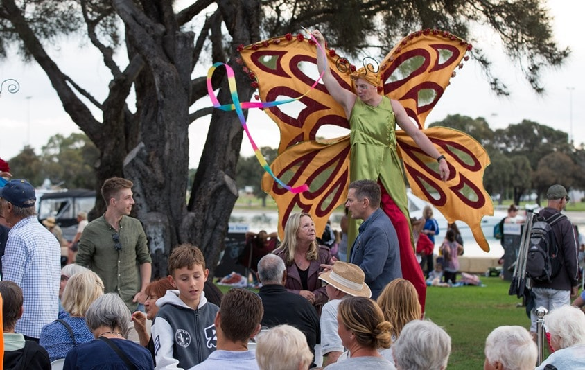 Stilt walker with large orange butterfly wings twirls a ribbon at people picnicking on the Eastern Foreshore