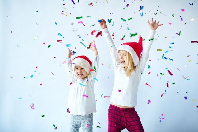 A young girl and boy in pyjamas and Santa hats throwing confetti into the air