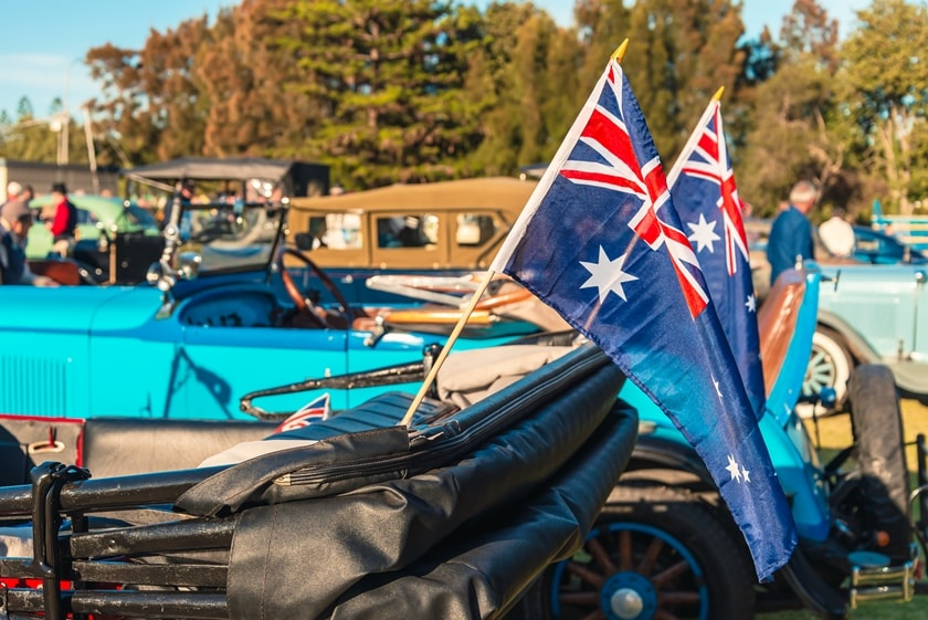 Two Australian flags on the back of a vintage car with the top down. Other vintage cars in the background.