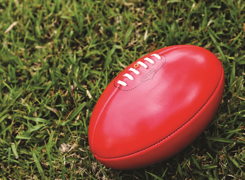 A red AFL football lying on the grass