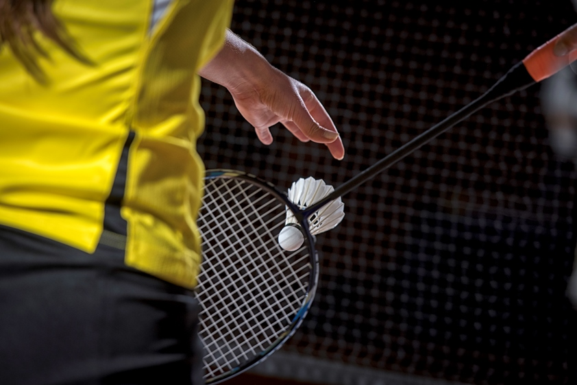 Close-up image of a person playing badminton