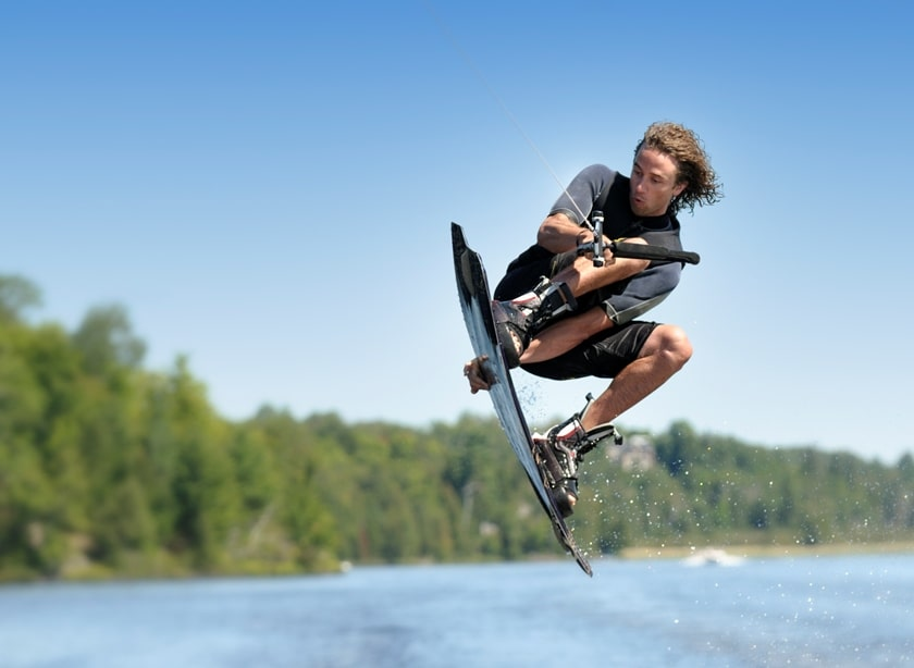 Man doing a jump while wakeboarding on a sunny day.