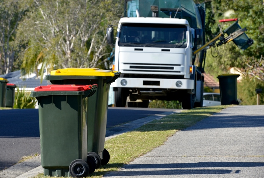 Rubbish truck coming down the street towards rubbish bins